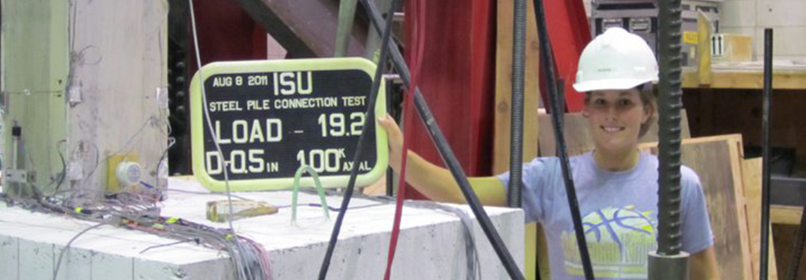 Jessica Garder shows load sign in a structural engineering laboratory