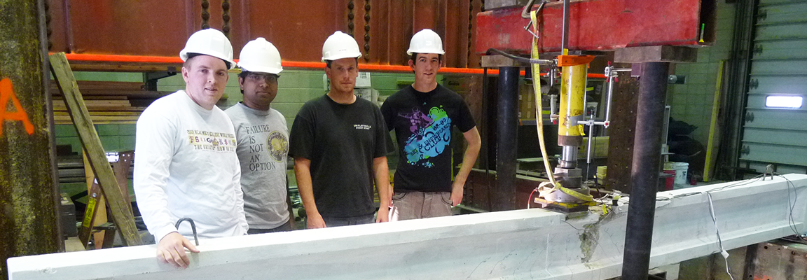 Students stand with concrete beam in engineering laboratory